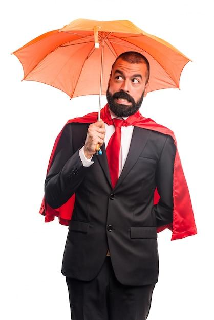 Homem de negócios super-herói segurando um guarda-chuva Foto gratuita