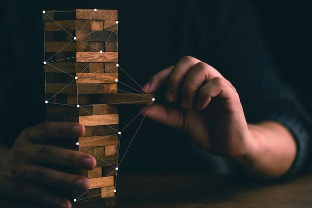 Homem de negócios tentar construir o bloco de madeira na mesa de madeira e fundo preto Foto Premium