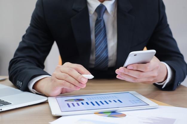 Homem de negócios, trabalhando no tablet pad e smartphone e laptop na mesa Foto Premium