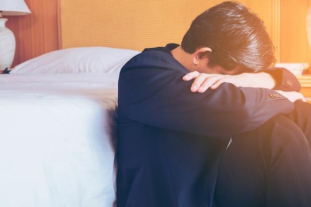 Homem de negócios triste sente-se no quarto de hotel Foto gratuita