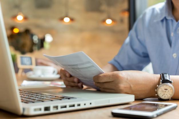 Homem de negócios usando laptop enquanto olha para a factura. Foto Premium