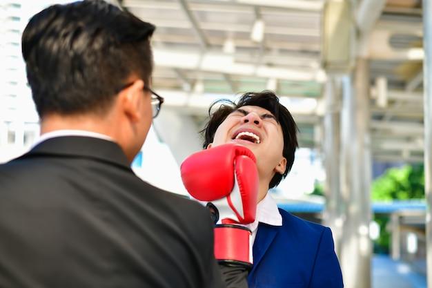 Homem de negócios usando luvas de boxe, jogando um soco. Foto Premium