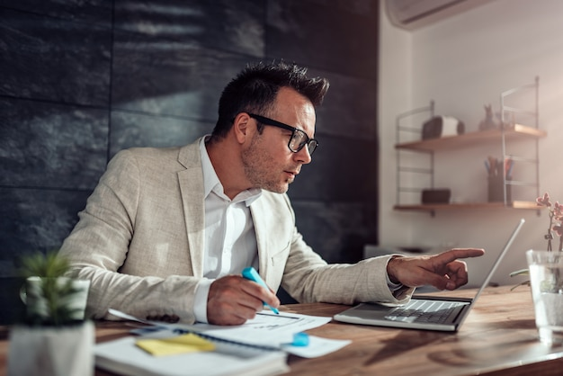 Homem de negócios usando o laptop e destacando o texto em seu escritório Foto Premium