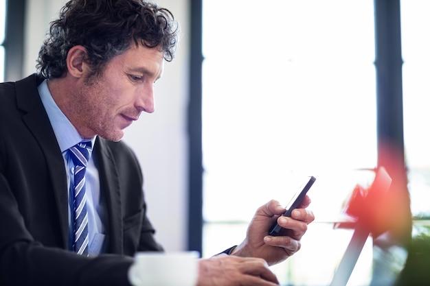 Homem de negócios usando o telefone enquanto trabalhava no laptop Foto Premium