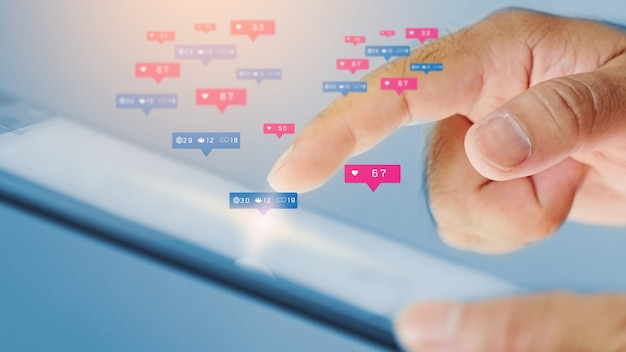 Homem de negócios usando tablet digital com ícones sociais na tela Foto Premium