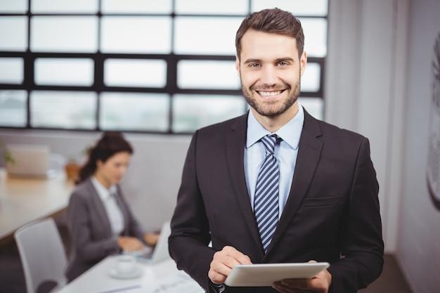 Homem de negócios usando tablet digital enquanto colega no fundo Foto Premium