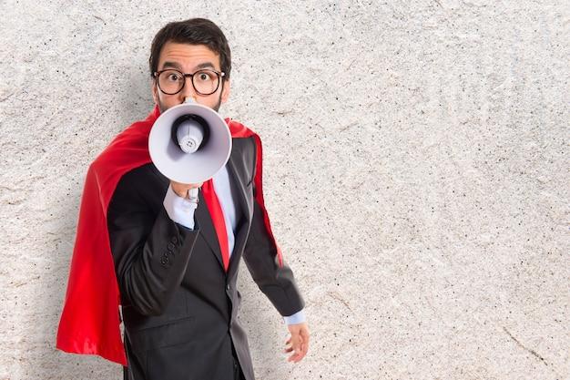 Homem de negócios vestido como super-herói gritando por megafone Foto Premium