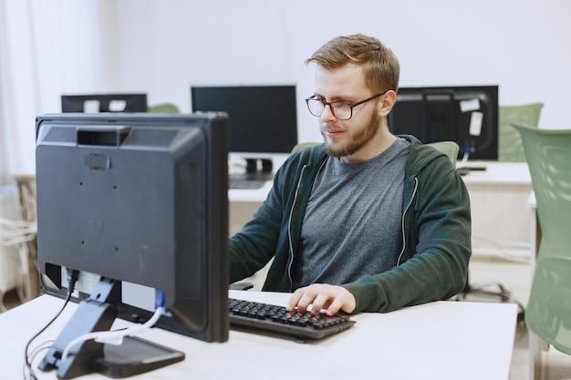 Homem de óculos. aluno na aula de ciência da computação. a pessoa usa um computador. Foto gratuita