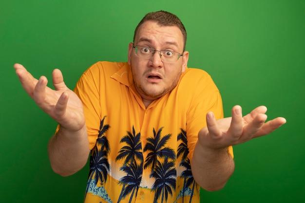 Homem de óculos e camisa laranja confuso com braços erguidos sem resposta em pé sobre uma parede verde Foto gratuita
