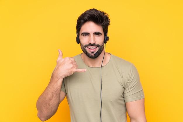 Homem de operador de telemarketing trabalhando com um fone de ouvido sobre parede isolada Foto Premium