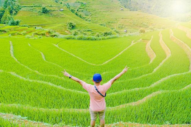 Homem de pé com as costas linda terraços arrozal arrozal e paisagem de montanha no sapa vietname. Foto Premium