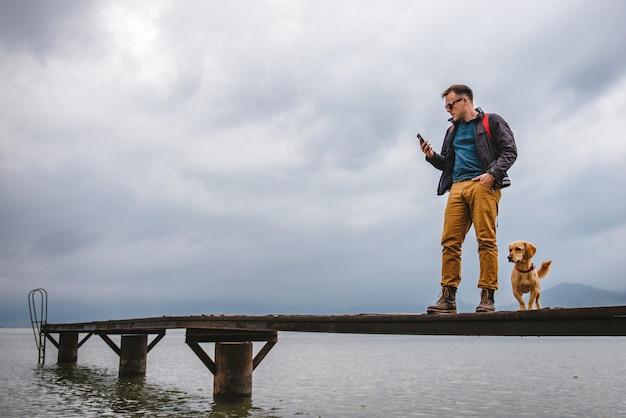 Homem de pé na doca e usando telefone inteligente Foto Premium