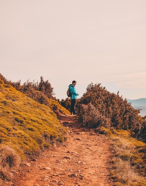 Homem de pé na estrada de terra Foto gratuita