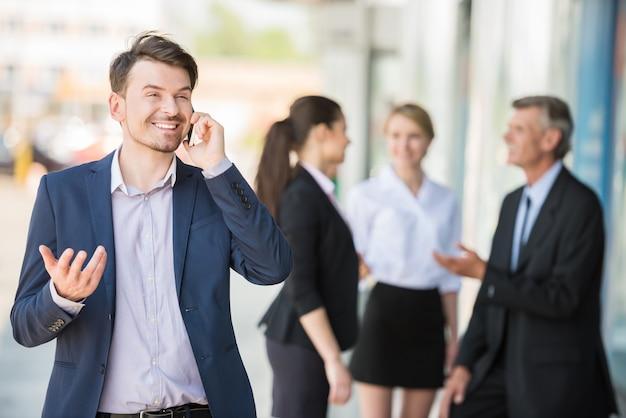 Homem de pé na frente do escritório e falando no telefone. Foto Premium