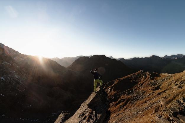 Homem de pé na pedra no topo da montanha de frente para o sol Foto gratuita