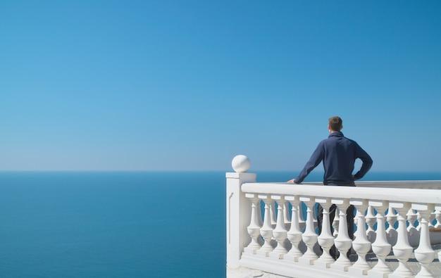 Homem de pé na varanda e olhar para o mar Foto Premium