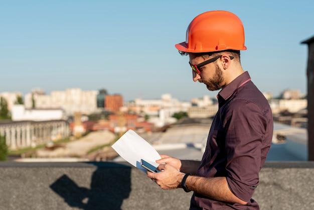 Homem de pé no telhado com telefone na mão Foto gratuita