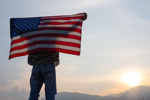 Homem de pé segurando a bandeira dos eua na vista do nascer do sol Foto gratuita