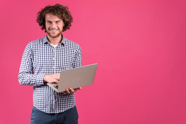 Homem de pé usando laptop Foto gratuita