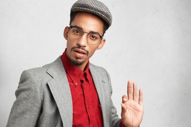 Homem de pele escura com óculos redondos, usa boné e camisa da moda antiga, mostra o sinal de ok, Foto gratuita