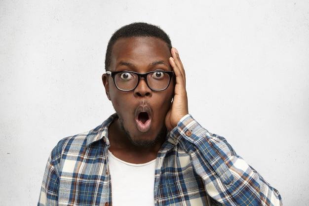 Homem de pele escura, de óculos escuros e camisa quadriculada, tocava a cabeça com total descrença, surpreso e chocado com notícias inesperadas positivas. expressões e emoções do rosto humano Foto gratuita