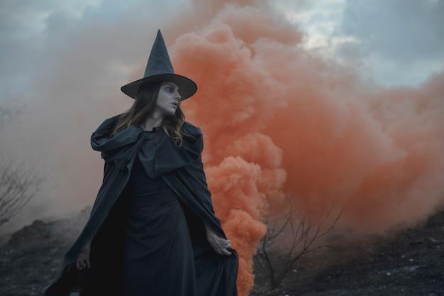 Homem de roupas witchy com lanterna, olhando para longe Foto gratuita