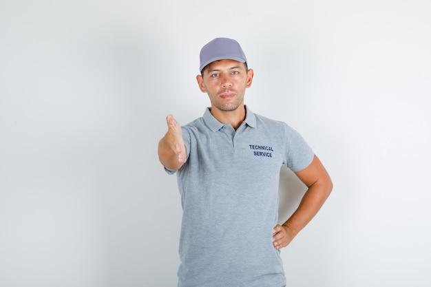 Homem de serviço técnico em camiseta cinza com tampa dando a mão para um aperto de mão Foto gratuita