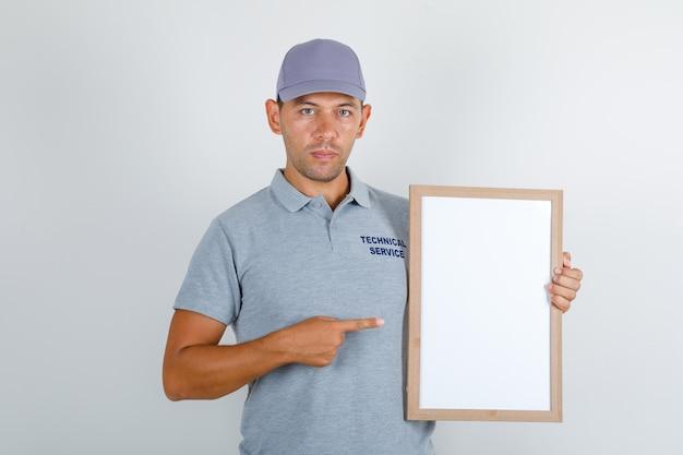 Homem de serviço técnico em camiseta cinza com tampa mostrando quadro branco Foto gratuita