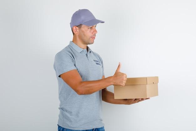 Homem de serviço técnico segurando uma caixa de papelão com o polegar para cima em uma camiseta cinza com tampa Foto gratuita