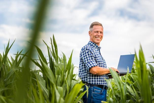 Homem de smiley de baixo ângulo vista com um laptop Foto gratuita