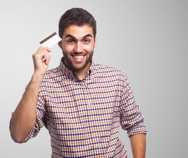 Homem de sorriso aberto que mostra o cartão de plástico. Foto gratuita