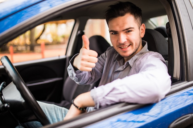 Homem de sorriso feliz que senta-se dentro do carro que mostra os polegares. cara bonito animado com seu novo veículo. expressão positiva do rosto Foto gratuita