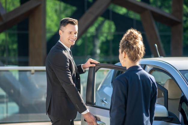 Homem de terno, abrindo a porta do carro, mulher em pé com as costas Foto Premium