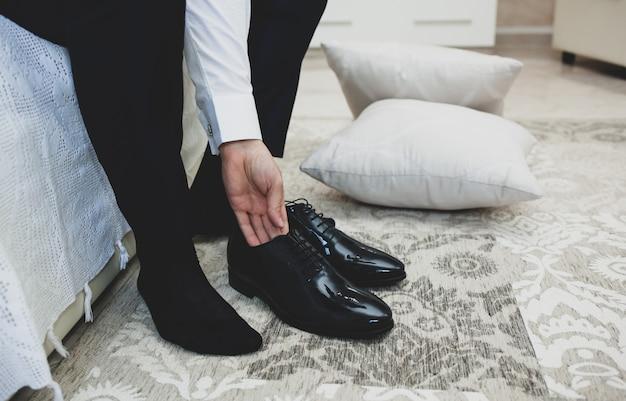 Homem de terno amarra cadarços em sapatos elegantes clássicos pretos. Foto Premium