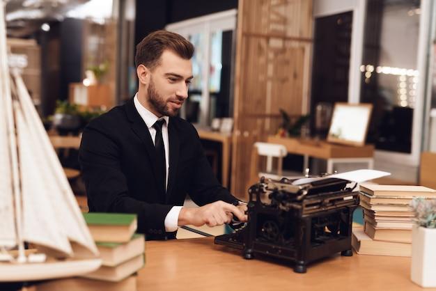 Homem de terno está sentado à mesa com uma velha máquina de escrever. Foto Premium