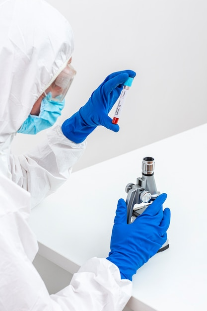 Homem de terno hazmat com amostra de sangue Foto gratuita