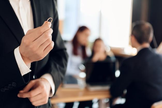 Homem de terno na mão segure o anel de noivado. Foto Premium
