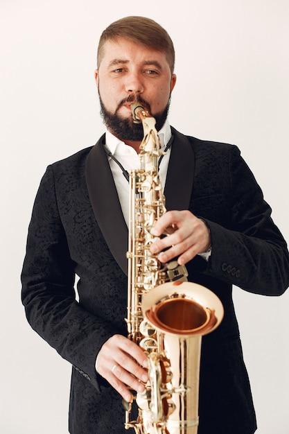 Homem de terno preto em pé com um saxofone Foto gratuita