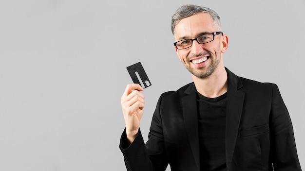 Homem de terno preto, segurando o cartão de crédito Foto gratuita