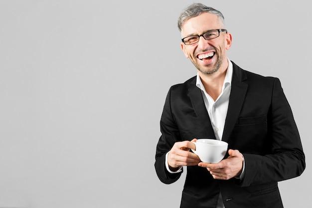 Homem de terno preto, segurando uma xícara de café e sorrisos Foto gratuita