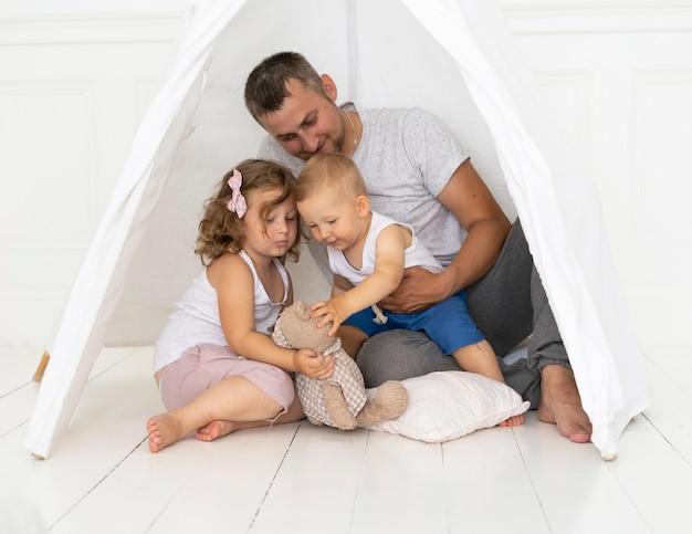 Homem de tiro completo, brincando com as crianças em uma tenda Foto gratuita