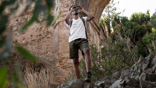 Homem de tiro completo com binóculo na natureza Foto gratuita