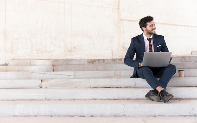 Homem de tiro completo nas escadas, trabalhando no laptop Foto gratuita