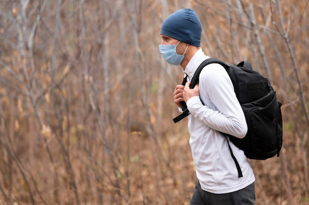 Homem de tiro médio com máscara facial e mochila na floresta Foto gratuita