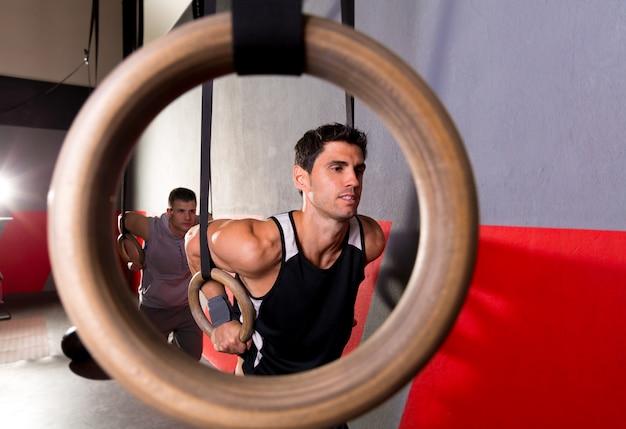 Homem de treino de anéis de mergulho de um buraco de anel no ginásio Foto Premium