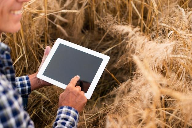 Homem de visão de ângulo de mock-up com um tablet Foto gratuita