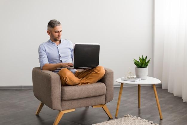 Homem de visão de longo prazo, usando seu laptop dentro de casa Foto gratuita