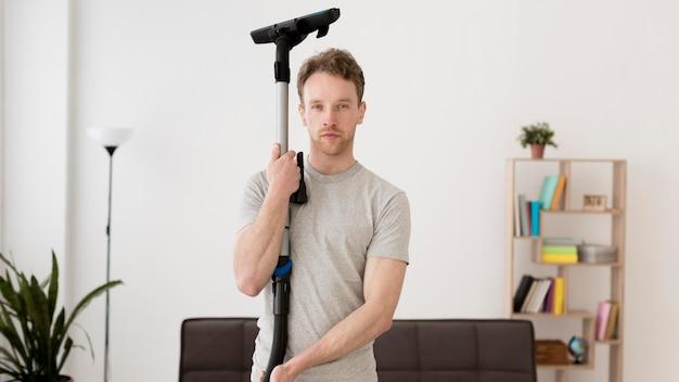 Homem de vista frontal com aspirador Foto gratuita