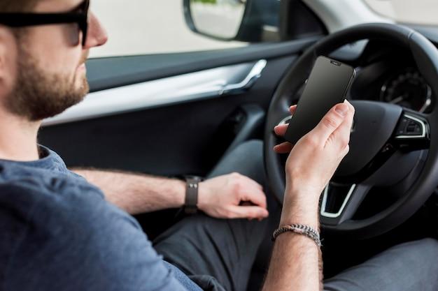 Homem de vista lateral verificando seu smartphone no carro Foto Premium