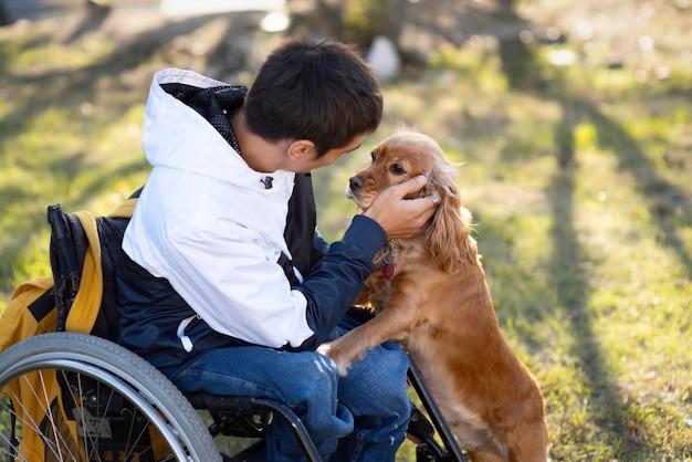Homem deficiente com tiro médio acariciando cachorro Foto gratuita